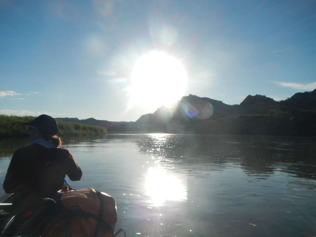 A person in a canoe floats down the river toward the sun. Mountains can be seen in the distance.